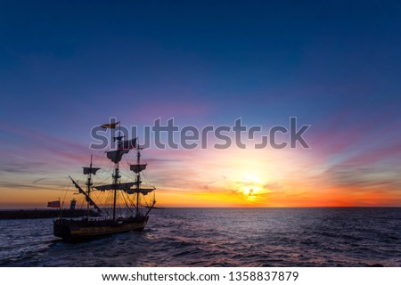 Silhouette of a pirate ship leaving the harbor for a long campaign on the ocean chasing, pirating other marchand ship