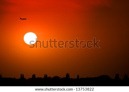Silhouette of a plane at sunset - stock photo