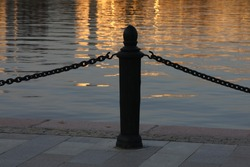 Silhouette of a pole with a chain on the pier against the background of Golden water at sunset.A wrought-iron fence.Decorative barrier on the sidewalk at the edge of the embankment in a light haze