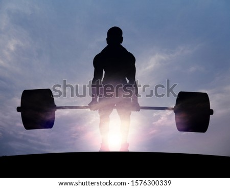 Silhouette of a powerful weightlifter lifting heavy weights against a surreal sunset sky. Double exposure composite illustration.