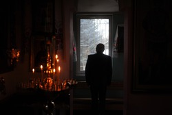 Silhouette of a priest standing before a bright window in the dark room with candles. Religion, christianity and belief concept.