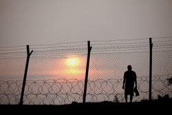 Silhouette of a prisoner behind a barbed wire fence in a concentration camp against fiery setting sun.