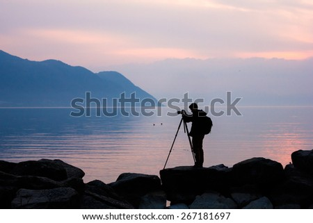 Silhouette of a professional photographer using a tripod, taking a photo of a mountain landscape