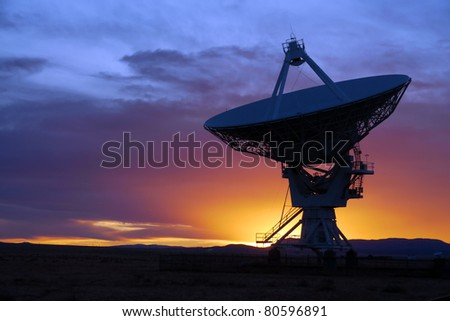 Silhouette of a radio telescope at the Very Large Array VLA in New Mexico USA at sunset