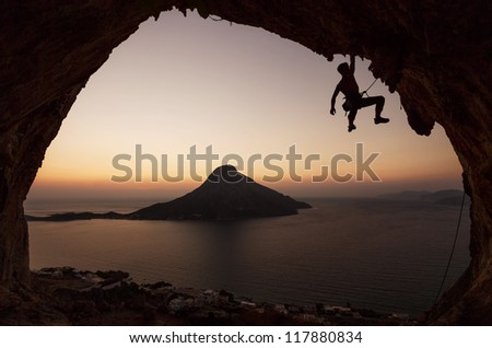 Silhouette of a rock climber against view of Telendos Island at sunset. Kalymnos Island, Greece.