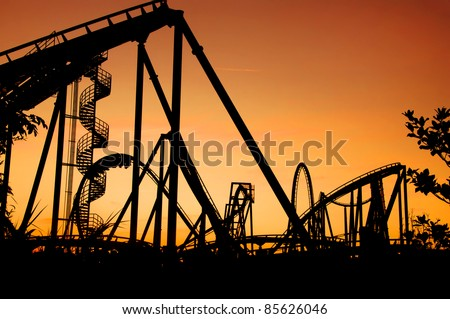 silhouette of a roller coaster during sunset at a fun fair