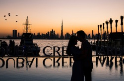 Silhouette of a romantic couple hugging at sunset in Dubai