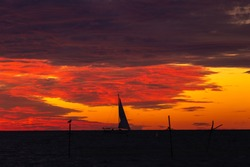 Silhouette of a sailing ship against the backdrop of a bright red cloudy, dramatic sunset sky