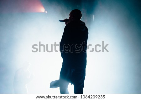 Silhouette of a singer on the stag. Silhouette of a rapper with a towel. Bright background.
