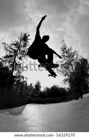 silhouette of a skateboarder doing a flip trick at the skate park.