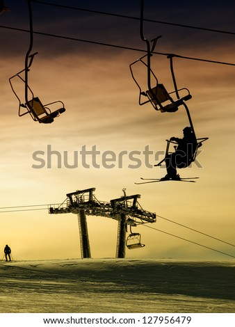 Silhouette of a skier on the ski lift above ski slopes at sunset.
