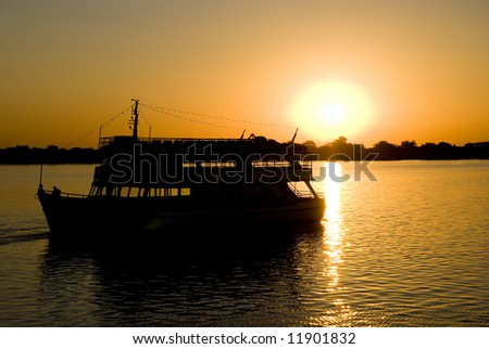 Silhouette of a small boat sailing away from setting sun, with deep orange hue.