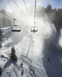 Silhouette of a snowboarder on a chairlift, going into misty and snowy section