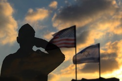 Silhouette of a soldier against the backdrop of the US flag and the flag of Israel. Soldier Silhouette in army uniform salutes friendship and alliance of the USA and Israel