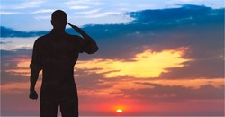 Silhouette of a soldier saluting during sunset.