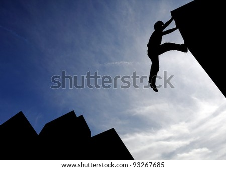 Silhouette of a sport boy scaling a wall in an urban surrounding against a blue cloudy sky for the concept of urban playground.