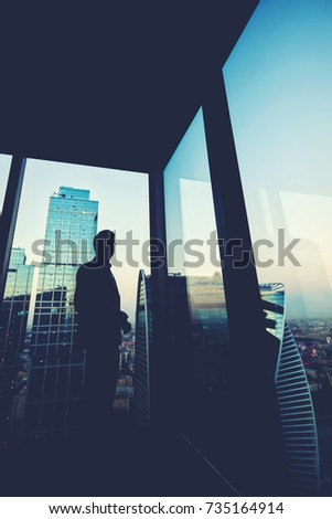 Silhouette of a successful man economist resting after work day while standing near big office window in modern interior, male intelligent lawyer relaxing after meeting with his partners