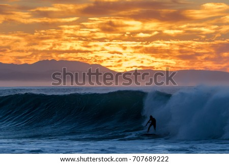 Silhouette of a surfer riding a wave at sunrise in Jeffreys Bay with mountains and the sun rising in the background