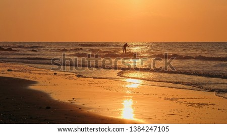 Silhouette of a surfer surfing with orange sky and glistening ocean