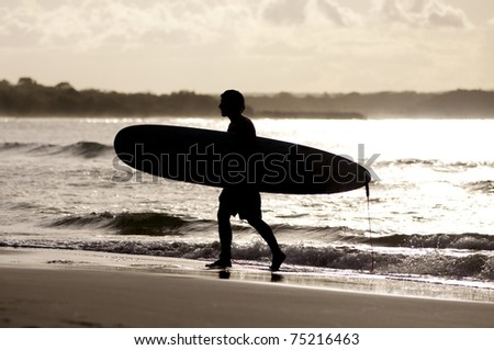 Silhouette of a surfer who carries his board at sunset