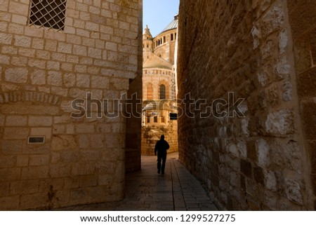 Silhouette of a tourist walking in an alleyway in the Old City of Jerusalem, Israel. The Old City is a 0.9 square kilometres walled area within the modern city of Jerusalem.
