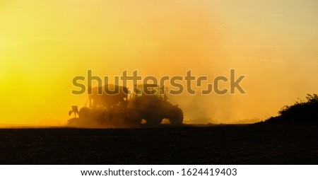Silhouette of a tractor sowing seeds in a field in a cloud of dust against the background of the setting sun.
