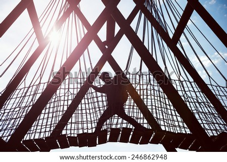 silhouette of a traveling man crossing over hanging bridge in bright sun