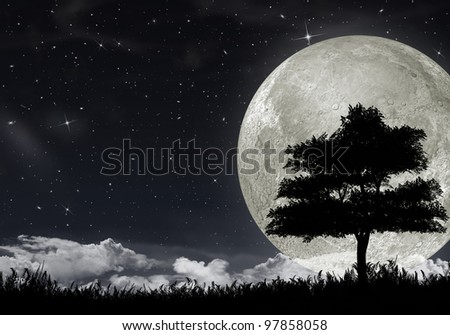 Silhouette of a tree against the big moon and the star night sky.