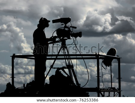 Silhouette of a TV cameraman against a cloudy sky
