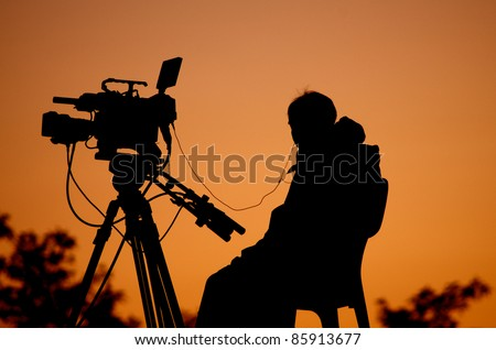 Silhouette of a TV cameraman against a sunset