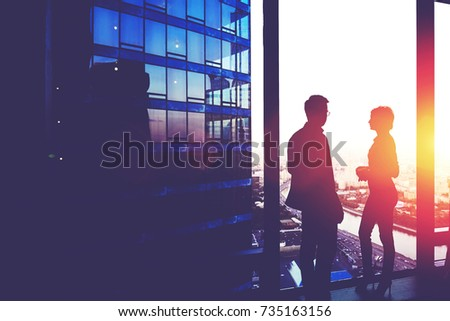 Silhouette of a two successful managing directors discuss ideas after meeting with partners while standing near big office window, young man and woman skilled economists relaxing after conference