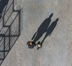 Silhouette of a two womans casting a long shadow on a cobble stone road