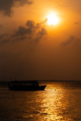 Silhouette of a typical maldivian boats a sunset sea.