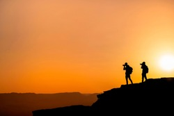 Silhouette of a unrecognizable photographers who shoots a sunset in the mountains. Photographer concept