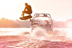 Silhouette of a wake skater as he launches off the wake behind a boat. Added lens flare and vintage filter.