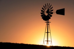 Silhouette of a windmill during sunset on a sunny day