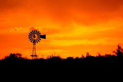 Silhouette of a windmill in front of a bright orange sunset.