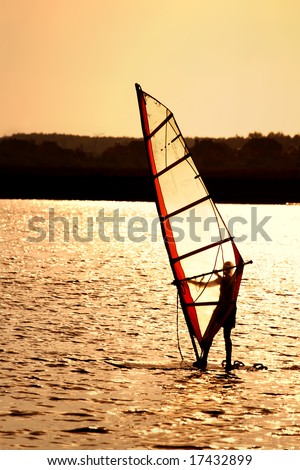 Silhouette of a windsurfing sail in the sunset