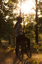 Silhouette of a woman biker in the forest in the rays of the sunset. Training in nature, escape from the city.
