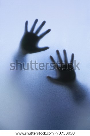 Silhouette of a woman body through frosted glass