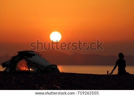 Silhouette of a woman camping with tents on the beach, Red sky sunset background.