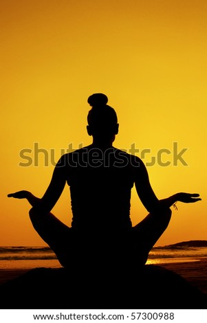 Silhouette of a woman doing yoga/meditation pose at sunset on the beach.