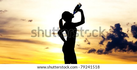 Silhouette of a  woman drinking water on the hill against yellow sky with clouds