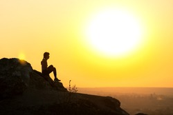 Silhouette of a woman hiker sitting alone on big stone at sunset in mountains. Female tourist on high rock in evening nature. Tourism, traveling and healthy lifestyle concept.