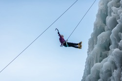 Silhouette of a woman hiking at a frozen waterfall, holding the ice axes and hanging on a climbing rope