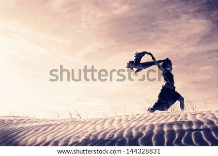 Silhouette of a woman holding a blowing scarf in the dunes.