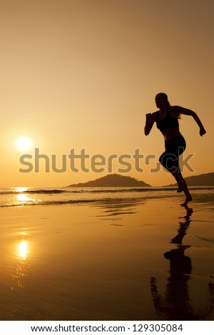 Silhouette of a woman jogging on the beach