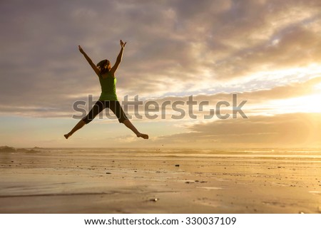 Silhouette of a woman jumping  on a the beach at the sunset #330037109