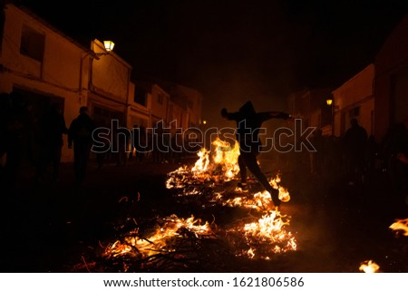 Silhouette of a woman jumping over bonfires at the traditional festivals of a small village. Festival concept
