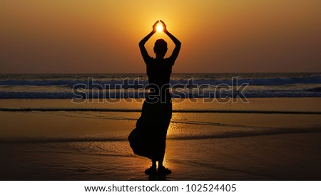 Silhouette of a woman on the background of sunset.